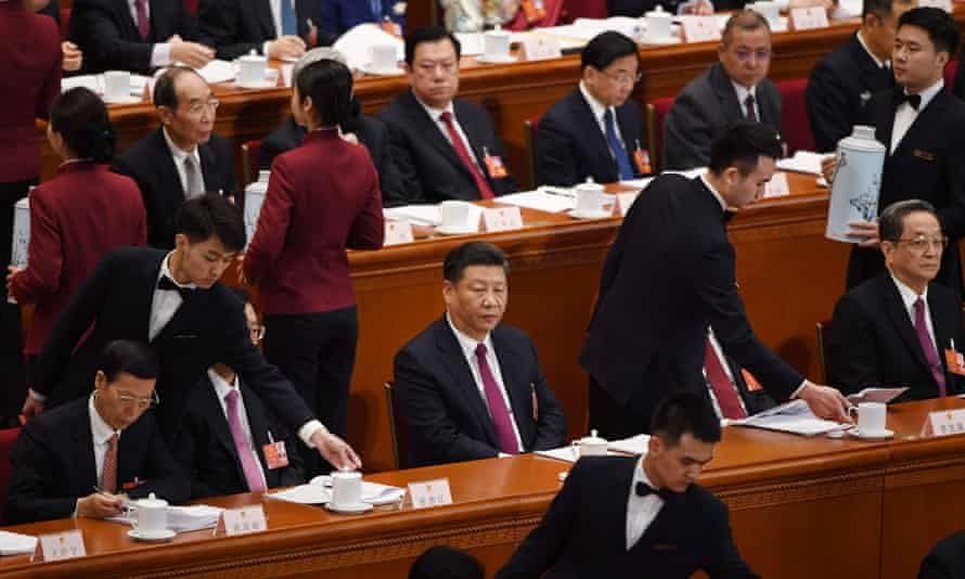 Chinese President Xi Jinping (C) looks on as tea is served during the opening session of the National People's Congress on Monday