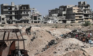 A Syrian government soldier walks past ruined buildings in Aleppo
