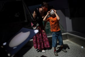 A woman and child observe the partial eclipse with special glasses at an observatory in Prague, Czech Republic. A projection of the eclipse from a telescope is seen in front
