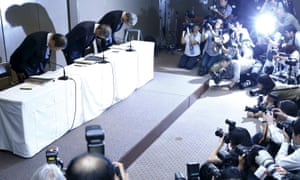 Hisao Tanaka, centre, with the chairman, Masashi Muromachi, left, and and executive vice president, Keizo Maeda, bow at the news conference in Tokyo.