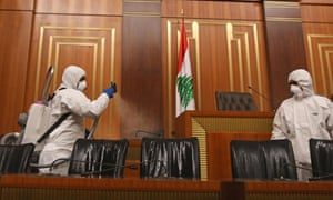 Sanitary workers disinfect the desks and chairs of the Lebanese Parliament in central Beirut amid the spread of coronavirus in the country.