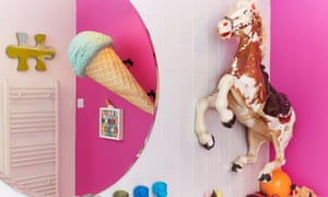 Pedro the pony and a large round mirror reflecting the giant ice cream on a bright pink wall in the bathroom