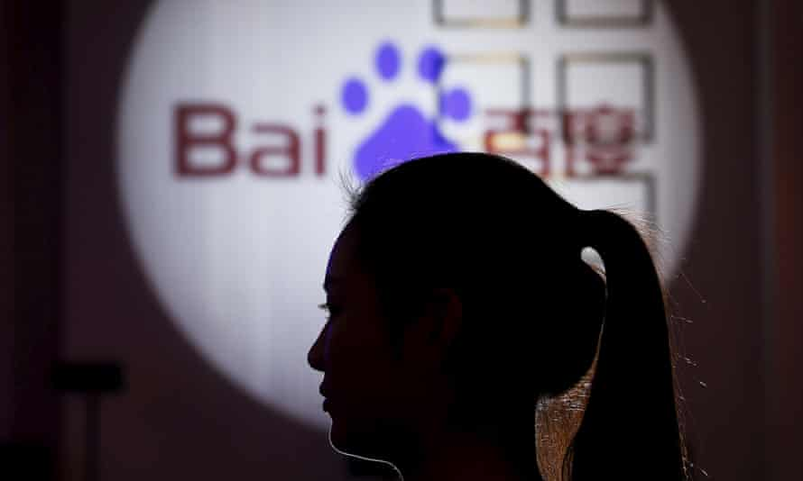 A woman is silhouetted against the Baidu logo at a new product launch from Baidu, in Shanghai. The internet giant has come under fire for allegedly promoting search results.