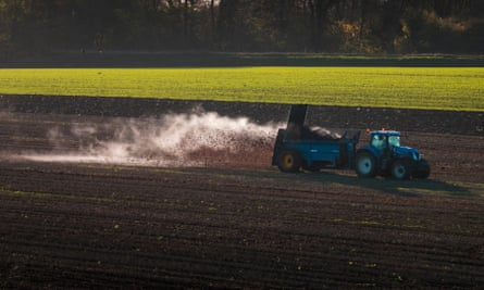 A tractor in a field spreading manure.
