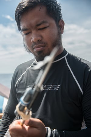 Eddy Setyawan, a Field Manager at the Sea Sanctuaries Trust, prepares his tagging spear ahead of a dive in the Ayau Islands, Raja Ampat, Indonesia