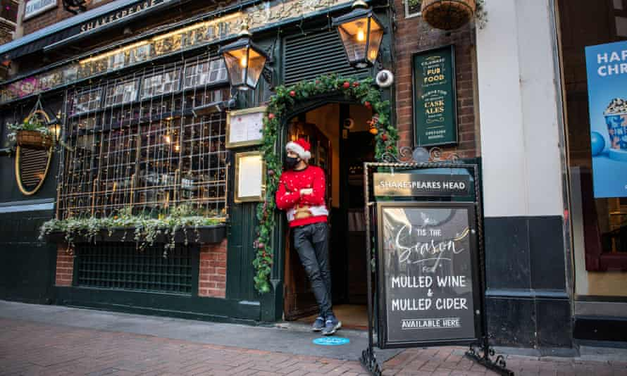 A pub worker waits to welcome people looking to order takeaway drinks in central London over the weekend.