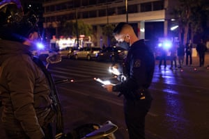 Athens, Greece, A policeman checks a driver's documents during a nightly curfew