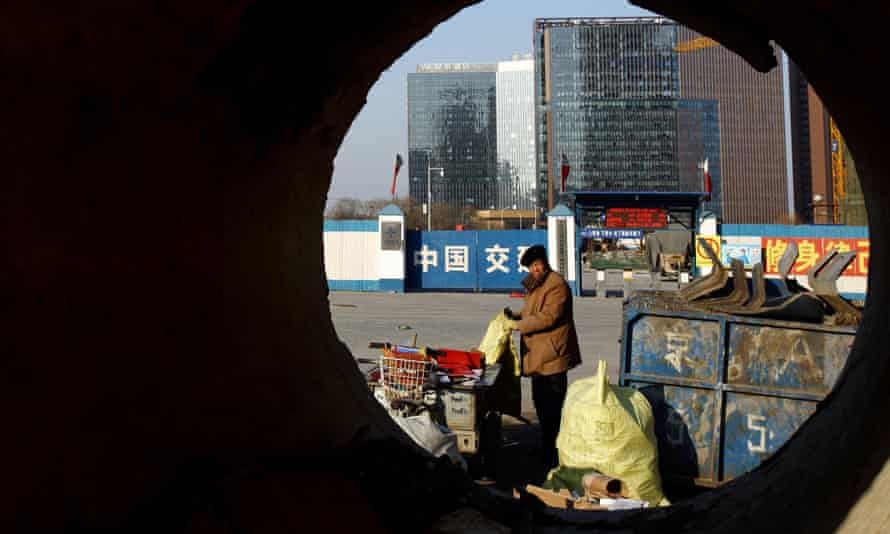 A waste picker collects waste at a commercial building construction site in Beijing, China.