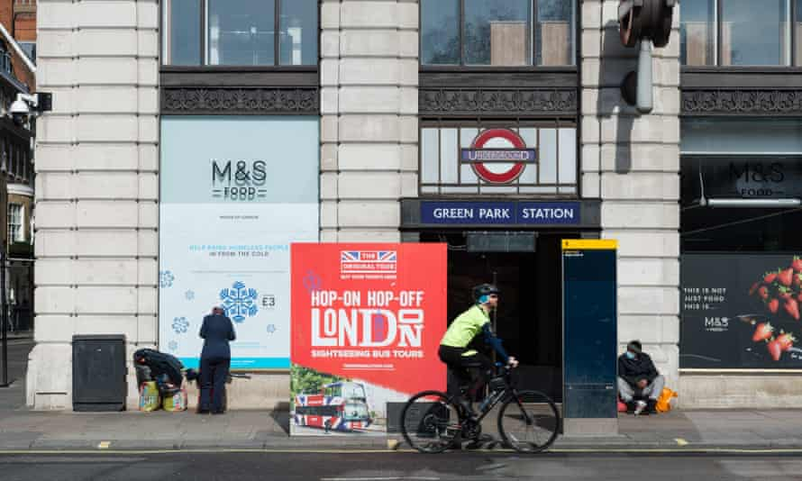 man rides a bicycle past homeless people along Piccadilly in central London as the UK's nationwide lockdown continued on 7 April 2020.