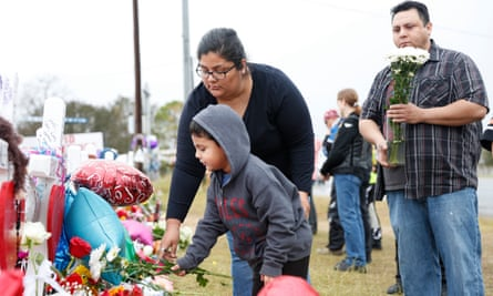 Liam, 4, and his parents Olivia and Leo leave flowers for the 26 people who died after a mass shooting in Sutherland Springs' First Baptist church.