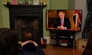 Members of a family listen as Britain's Prime Minister Boris Johnson makes a televised address to the nation from inside 10 Downing Street in London on March 23, 2020.