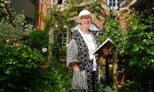 Sarah Hosking, fundraising to help women writers, reading a book in her cottage garden.