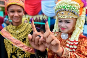 Indonesians show their inked fingers after casting their vote at a polling station in Trumon, Southern Aceh province.
