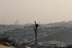 A boy stands on a roof to fly a homemade kite in Kutupalong refugee camp.