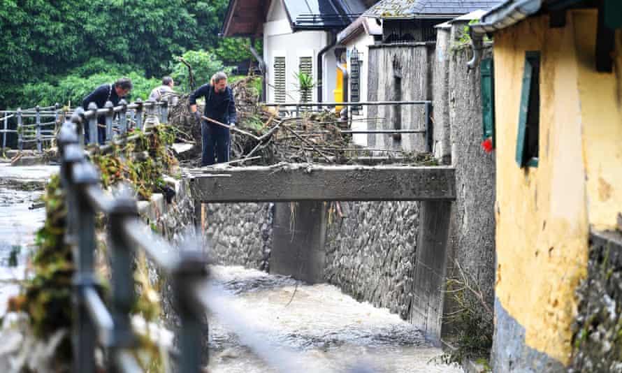 Mężczyźni oczyszczają most z błota i gruzu w Hallen w Austrii, po zalaniu zabytkowego centrum.