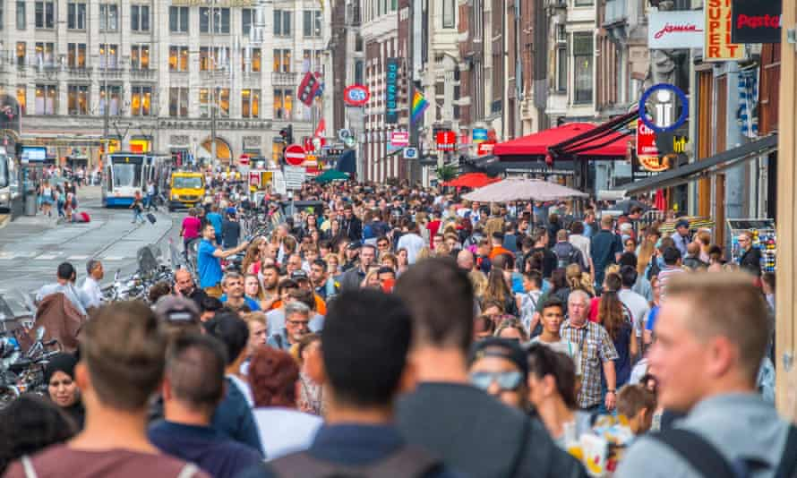 Huge crowd of tourists at famous Damrak street in Amsterdam.