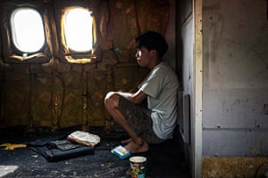A young man sits in the hull of the plane that he calls home. His familyhave lived in the abandoned planes for years
