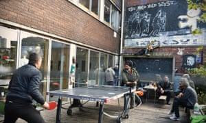 Men play table tennis in a Bristol pub garden that features The Mild Mild West, a Banksy mural that depicts a teddy bear throwing a Molotov cocktail at riot police.