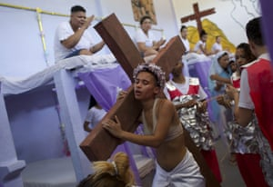 A woman carries a cross as part of performance