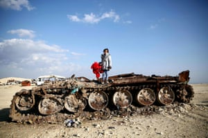 Rawan, an 11-year-old Syrian girl, poses on a destroyed tank with her stuffed bear near a village about 6km from the Bab al-Salamah border crossing between Syria and Turkey in the north of Aleppo province