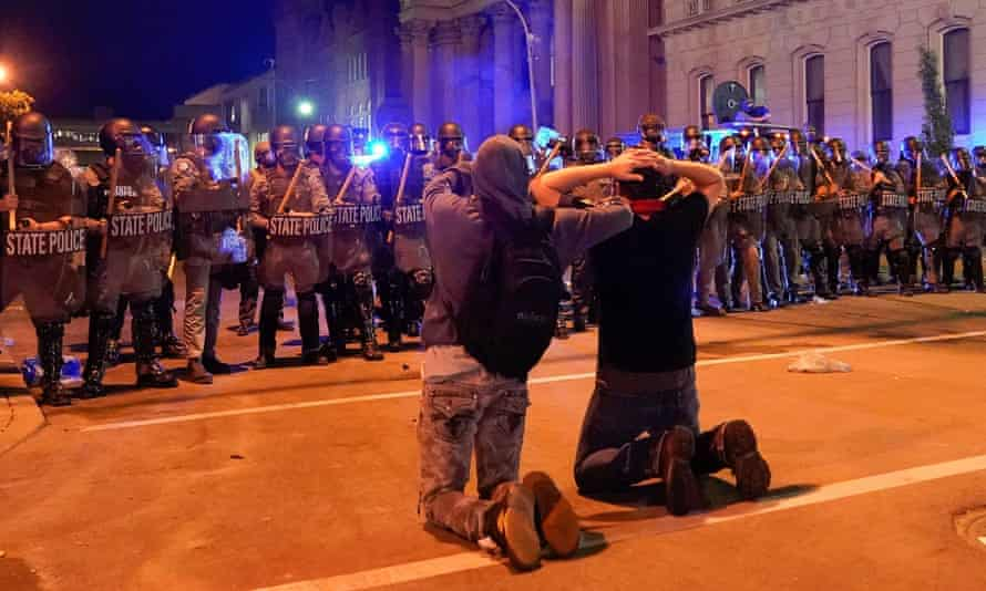 Two men kneel in front of a line of state troopers during a protest in Louisville, Kentucky, on 1 June.