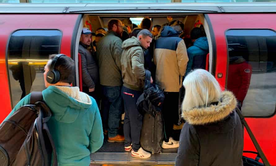 Passengers squeeze on to a busy Central Line underground train this morning at Stratford station in London