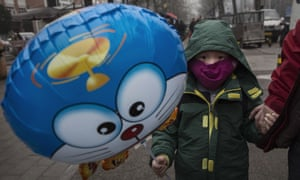 A Chinese boy wears a mask as he carries a balloon