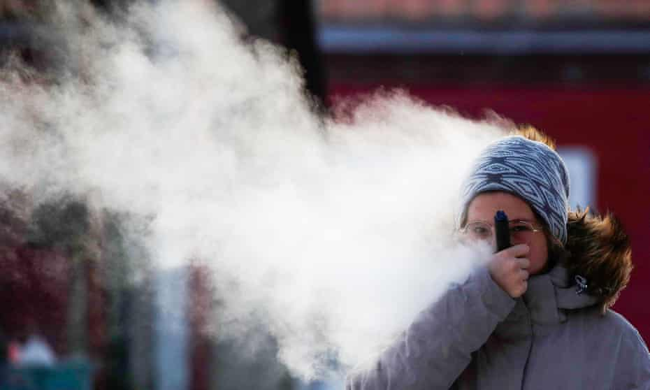 A woman vaping in a street.