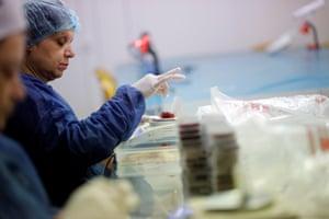 A worker weighs one gram of dried saffron stigmas