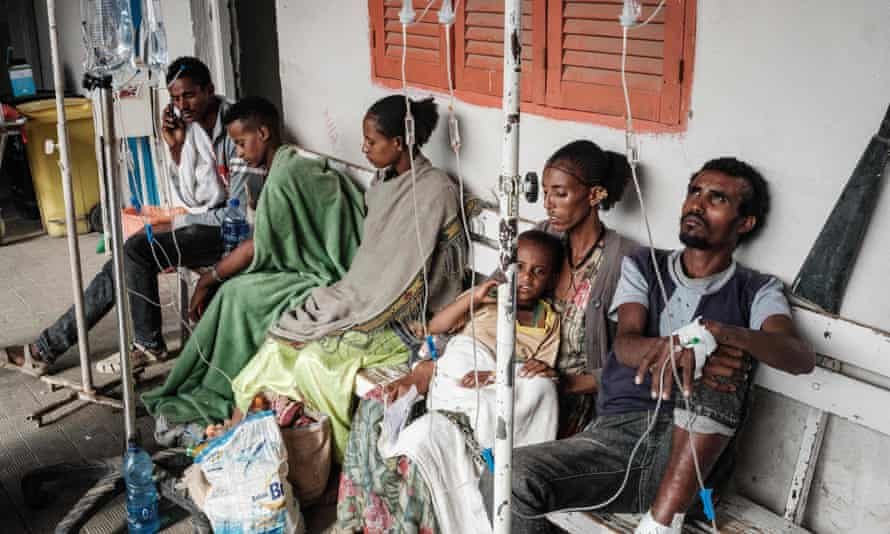 People who were injured in their town Togoga in a deadly airstrike on a market, wait on a bench for medical treatment.