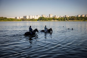 Women cool their horses off in the water at Borisovskye Ponds