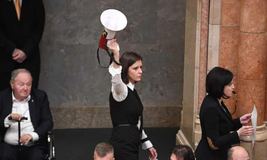 Hungarian MP Bernadett Szél (centre) holds a siren-horn next to Agnes Kohalmi (in protest against a 'slave law' that loosens labour rules.