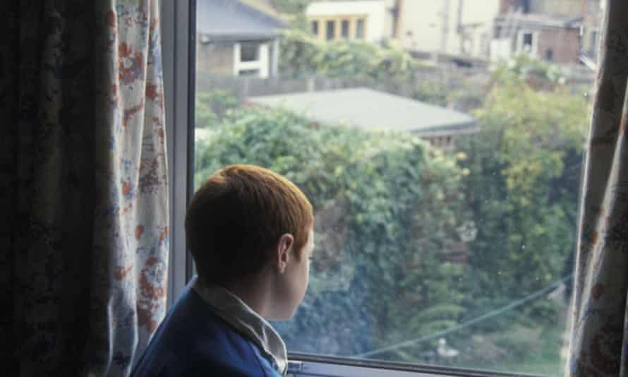8 year old boy looks out of bedroom window