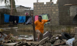 A man balances on rubble surrounded by flood waters in Beira, Mozambique