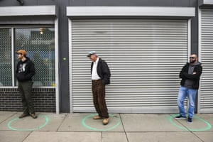 People stand in freshly painted circles, 6ft apart, as they wait in a two-hour line to buy marijuana products in Denver.