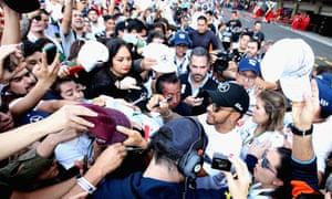 Lewis Hamilton obliges autograph hunters in the pit lane of Autodromo Hermanos Rodriguez.