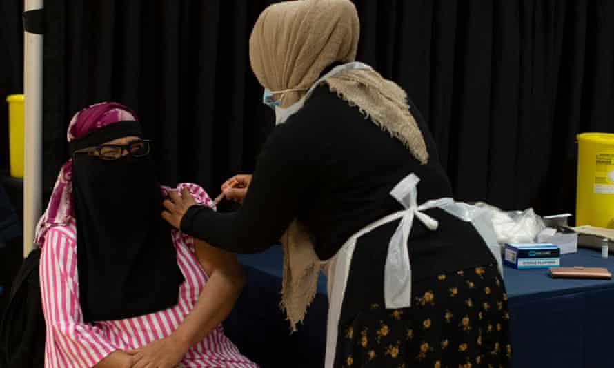 A woman receives the AstraZeneca vaccine at the East London Mosque.