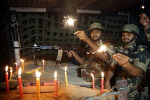 Indian border security force soldiers burn firecrackers in their bunker during celebrations in Akhnoor, Kashmir