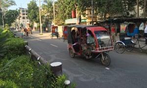 A battery-powered auto-rickshaw drives down a street in Rajshahi, Bangladesh.