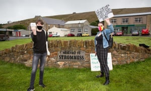 Two protesters waiting for Boris Johnson during his visit to Stromness, Orkney.