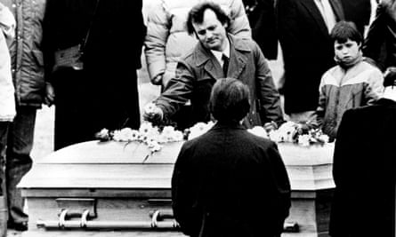 Actor Bill Murray places a flower on Belushi's coffin at his funeral in 1982.