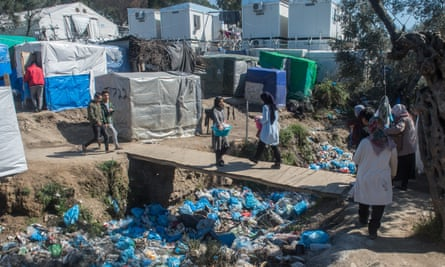 People cross a bridge over bags of waste in the Moria camp in May