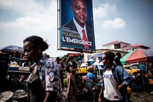 Women pass a poster of Emmanuel Ramazani Shadary