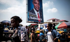 Women walk past a campaign poster of Joseph Kabila's chosen successor as president of DRC Emmanual Ramazani Shadary in Kinshasa on 18 December 2018