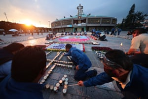 Staff of the Basilica of Guadalupe light candles with messages placed by Catholics prior to the celebration in the central area of the Basilica as part of the Day Of Our Lady Of Guadalupe Celebrations at Basilica de Guadalupe on 11 December, 2020 in Mexico City, Mexico.