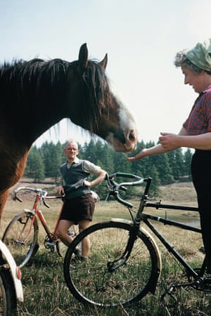 A couple make friends with a horse during their bike ride in May 1959