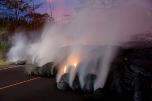 Volcanic gases rise from Kilauea lava flow that crossed Pohoiki Road by Highway 132, near Pahoa, Hawaii