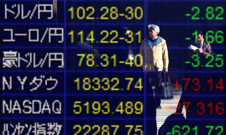 A man is reflected in an electronic board showing exchange rates between the Japanese yen against the US dollar and other market indices in Tokyo.