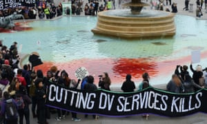 Sisters Uncut protest in London's Trafalgar Square where fountains have been dyed red over cuts to domestic violence services
