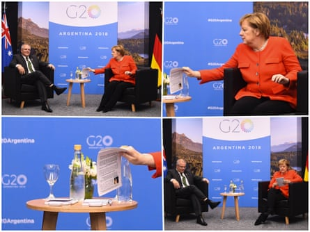 Angela Merkel checks notes with information about her counterpart.